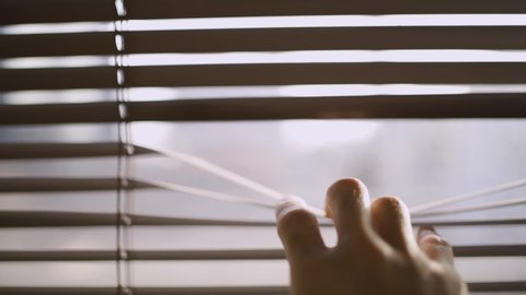 Close up of a hand reaching and opening a crack in the window blinds