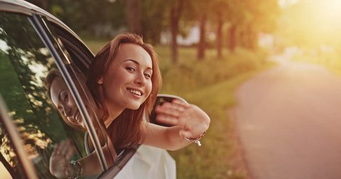 Woman waving someone from the car. Filmed in 4K DCi resolution. Young woman in a car greeting someone, winking and waving hello or goodbye. Leaving for a road trip journey. Slow motion.