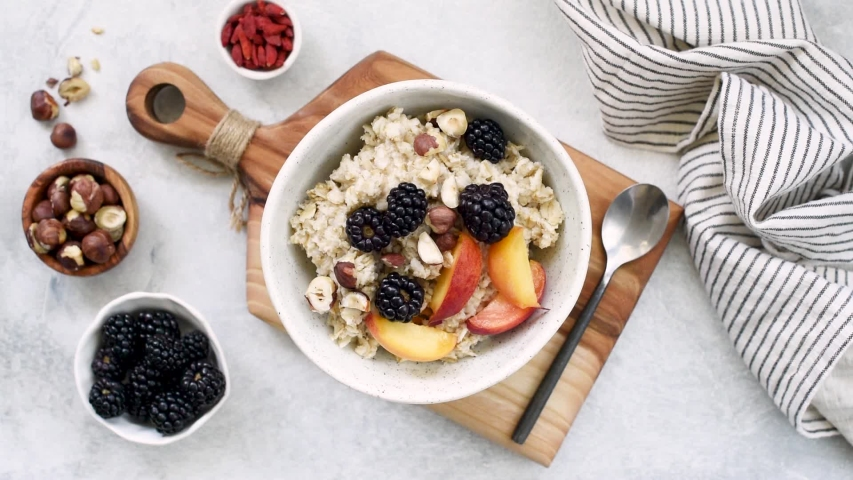 Stop motion animation oatmeal porridge with fruits and nuts for healthy breakfast. Table top view. Clean eating, dieting, weight loss concept
