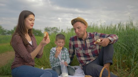 picnic, cheerful female feeds buns man buns while relaxing with kid boy milk drinker at family picnic outdoors in green field close up against sky