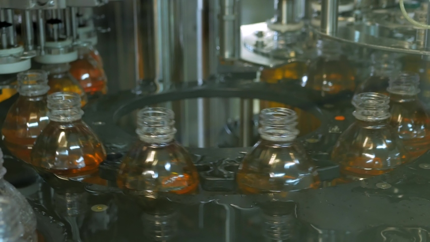 Plastic bottles inside industrial machine conveyor line or belt preparing for filling with drink. Water and juice bottling plant.   Shutterstock HD Video #1030823096
