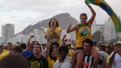 Copacabana, Rio de Janeiro/Brazil - 30th December 2014: Good-looking young millennial male and female Brazilian soccer fans celebrating on friends shoulders in crowd waving national flag