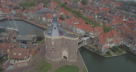 Aerial circling the Drommedaris Defence tower in historic Dutch town Enkhuizen in North Holland the Netherlands with Dutch flag flying revealing the white wooden drawbridge