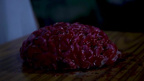 A brain with blood all over it, on the table being stab by a knife.