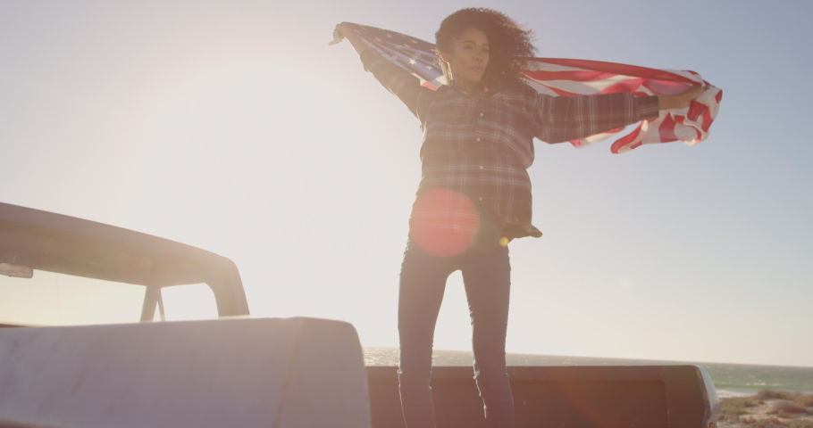 Low angle view of African american woman standing with waving american flag on a pick up truck