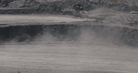 Big yellow heavy truck in open cast mine mining of coal the overall plan. Open pit anthracite mining, mining truck at work working in quarry. Dumpers quarrying industry mining work of machinery trucks