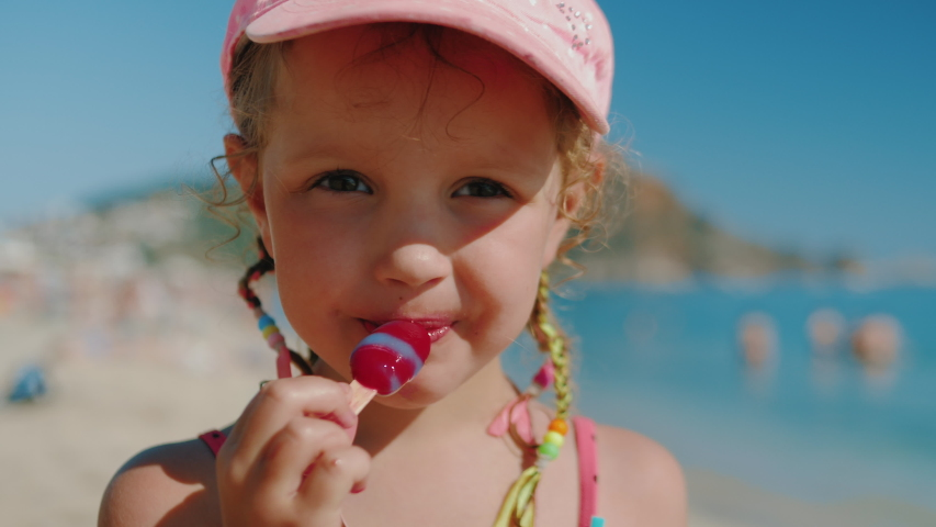 Caucasian cute little girl in pink bathing suit and cap and with multi-colored pigtails eating ice cream on the beach. Close up, 4k, slow motion. | Shutterstock HD Video #1031031806