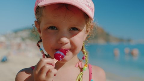 Caucasian cute little girl in pink bathing suit and cap and with multi-colored pigtails eating ice cream on the beach. Close up, 4k, slow motion.