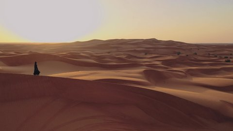 Aerial view from a drone flying next to a woman in abaya United Arab Emirates traditional dress walking on the dunes in the desert of the Empty Quarter. Abu Dhabi, UAE.