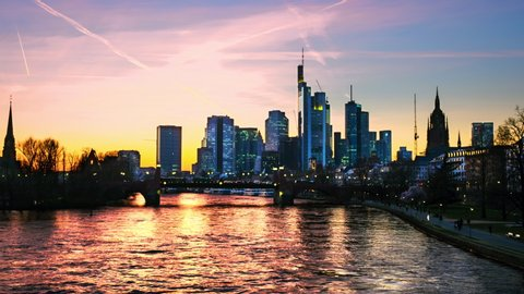 Frankfurt am Main, Germany. Skyline of Frankfurt, Germany in the sunset with famous illuminated skyscrapers and river. Time-lapse of cloudy sky at night, zoom in