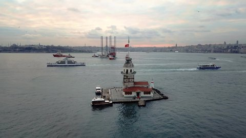 Aerial of Maidens Tower, one of the most iconic buildings of the Istanbul City. An oil platform rig underway through Bosphorus Sea on sunset