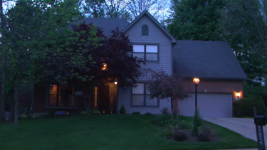Establishing shot of the front of a nice middle class house framed by bushes and tree branches; springtime and in the evening.  This is part of a set of shots of the same house in all seasons.