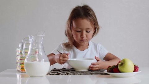 Portrait of small cute tanned kid girl eats with pleasure her breakfast. She has a cornflakes with milk sitting at table on white background.
