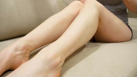 Young slim girl performs epilation of legs at home. Electric epilator for hair removal.