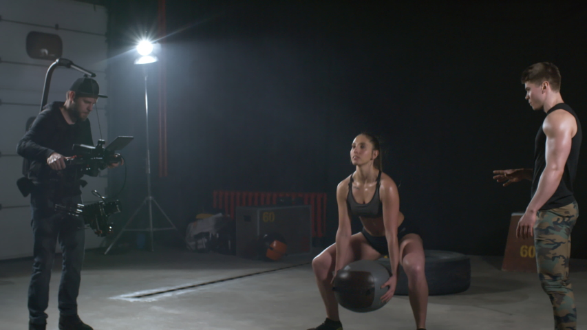 Sequence of shots of athletic young woman demonstrating weighted sumo squats and man talking to camera while camera crew recording video about sports
