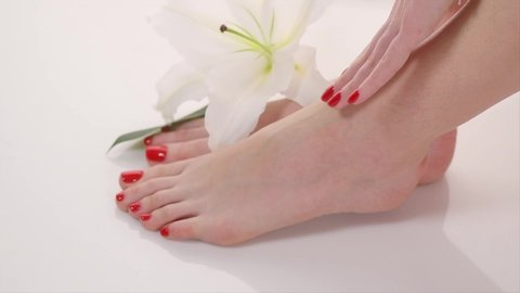 Manicure and Pedicure in beauty salon. Spa, skin care, moisturizing concept. Healthy Female hands and legs with beautiful nails. Soft skin, skincare concept. Beauty nails, varnish. Slow motion 4K UHD