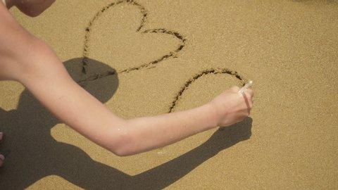 Girl drawing heart symbol on sand beach.