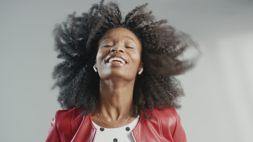 Attractive Black Girl Posing for a Fashion Magazine Photoshoot. Beautiful Girl Smiles during Professional Studio Photo Shoot for Fashion Magazine. She Wears Red Faux Leather jacket