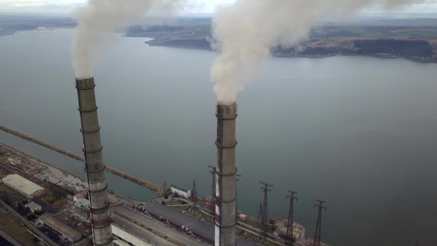 Aerial view of high chimney pipes with grey smoke from coal power plant. Production of electricity with fossil fuel.