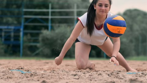 Young female athlete dives into the sand and saves a point during beach volleyball match. Cheerful Caucasian girl jumps and crashes into the white sand during a beach volley tournament