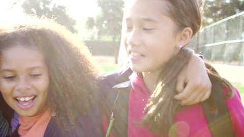 Slow motion sequence as camera pans along line of children hanging out with friends in park.Shot on Sony FS700 at frame rate of 100fps