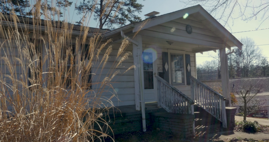 Establishing shot of a small one story house with tall dead grass in the foreground - dolly shot