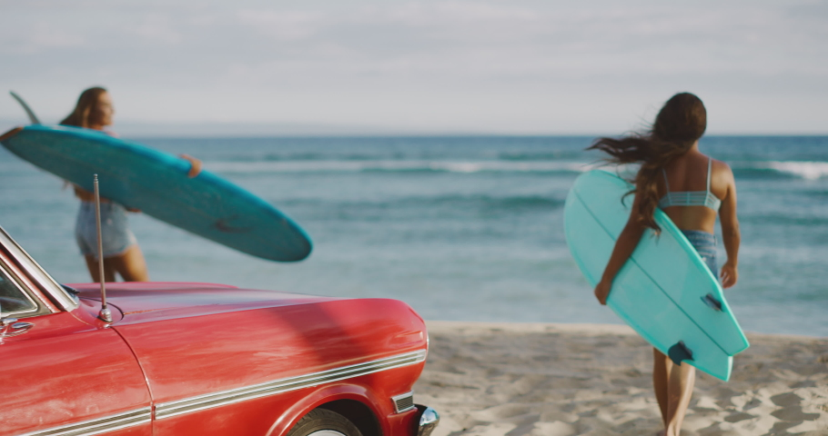 Young attractive women at the beach with vintage beach cruiser car, getting ready to surf at sunset, island beach lifestyle | Shutterstock HD Video #1031878346