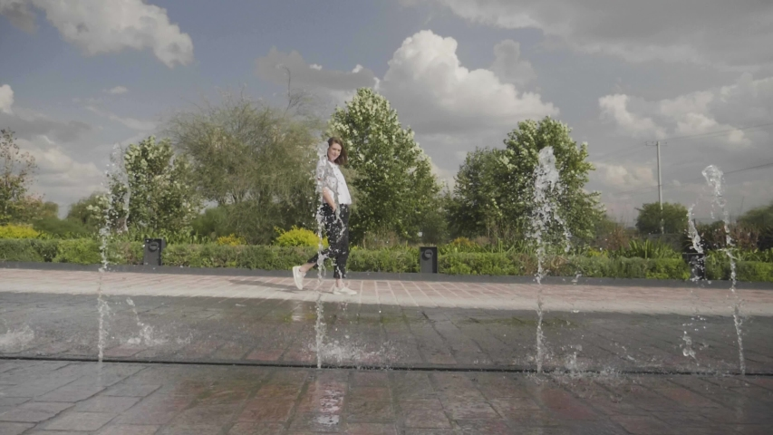 Slow Motion Woman Walking by Water Fountain | Shutterstock HD Video #1031881946