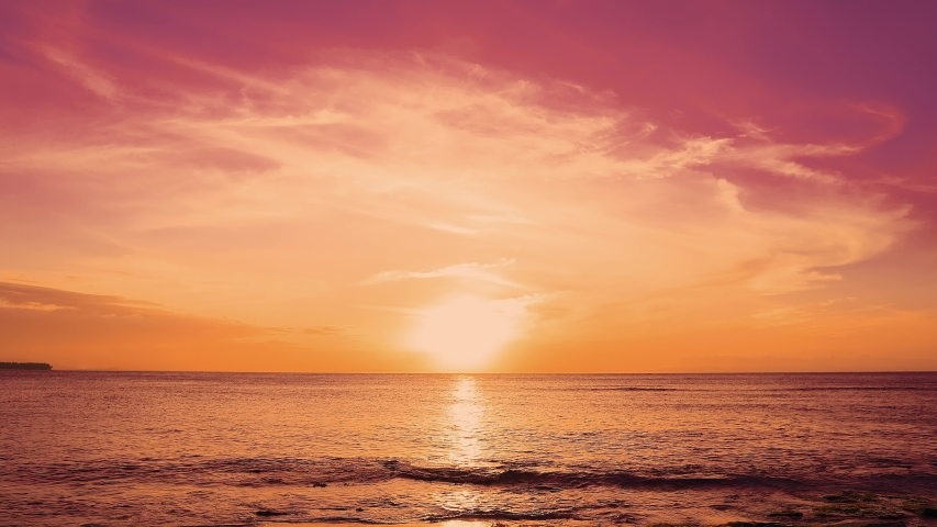 Red sundown sea. The coast of the Caribbean Sea, the yellow sun touches the horizon, beautiful orange clouds around the sun. Amazing view from the beach to the red sundown sea. Beautiful sea landscape #1031884796