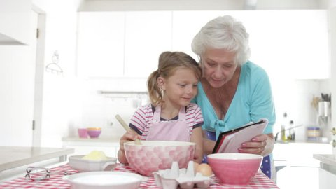 Grandmother reads recipe before showing granddaughter how to mix ingredients together which she then copies.Shot on Canon 5D Mk2 at at a frame rate of 25 fps