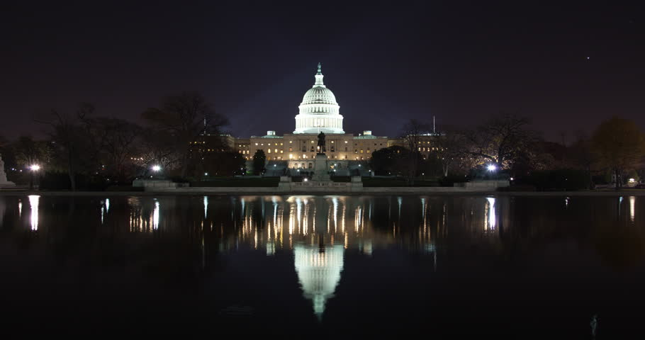 Timelapse of the United States Capitol building in Washington DC at night from across the Tidal Basin at night all lit up.  Reflection of building in the water in the shot.