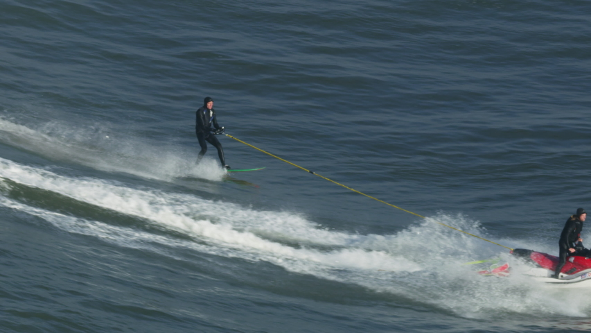 California, USA - February, 2019: Aerial view of jet ski towing athletic surfer riding on wave RED WEAPON | Shutterstock HD Video #1032009626