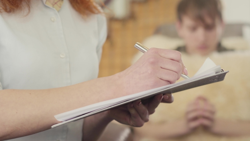 Young guy at a reception with a psychotherapist. The female hand of an unrecognized psychologist is writing something down in a notebook or in a patient card. | Shutterstock HD Video #1032078656