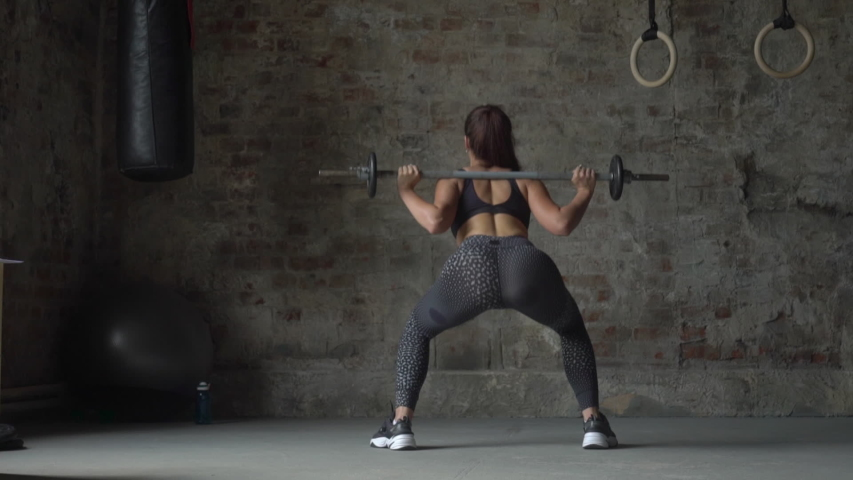 Back view of woman in black sportswear holding bar making weight-lifting exercise on the background of a brick wall | Shutterstock HD Video #1032187046