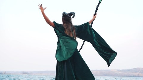 Mysterious girl with long bleached hair on shore, lady in long green flying  dress, terrible powerful witch in emerald mantle and magic staff invokes  storm and storm with spell, from back without face