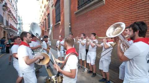 PAMPLONA/SPAIN - JUNE 2019: Young Spanish people and friends getting ready for the Festival of San Fermin in Pamplona, Navarra, Spain. Culture and tradition in Europe with band playing music