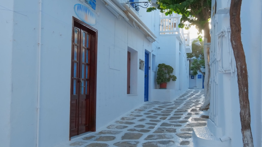 Walking with steadycam steadicam in picturesque scenic narrow streets with traditional whitewashed houses with blue doors windows of Mykonos town in famous tourist attraction Mykonos island, Greece | Shutterstock HD Video #1032229466