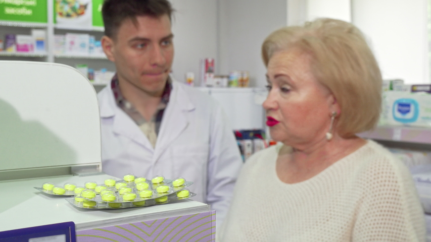 Senior woman asking pharmacist about medicine she is buying | Shutterstock HD Video #1032306596