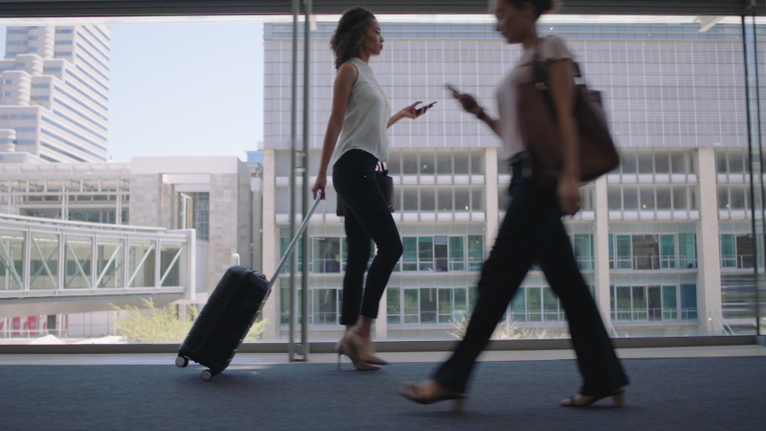 Young business woman traveler walking using smartphone pulling trolly bag in airport texting checking messages female commuter traveling international for business trip 4k