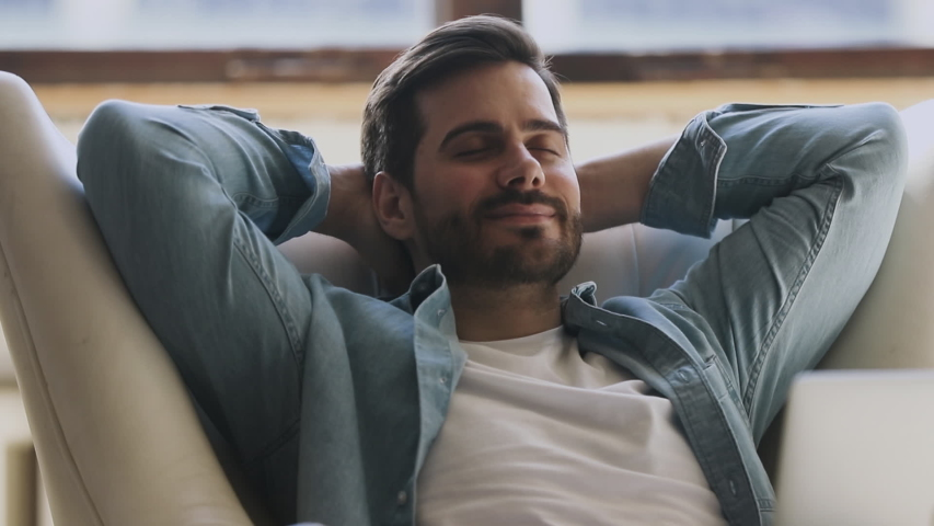 Calm happy healthy young man resting holding hand behind hand eyes closed lean on comfortable armchair, relaxed serene guy breathing fresh air lounge on chair enjoy stress free peaceful nap at home #1032517136