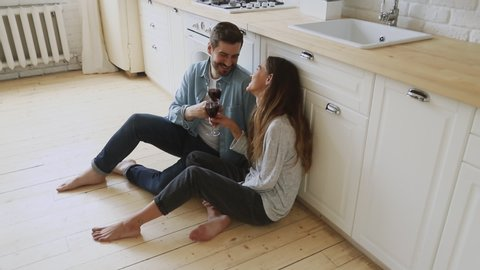 Affectionate young family couple happy husband and wife sit on cozy kitchen room floor hold glasses drink red wine talk laugh celebrate holiday new home purchase rent mortgage investment, above view