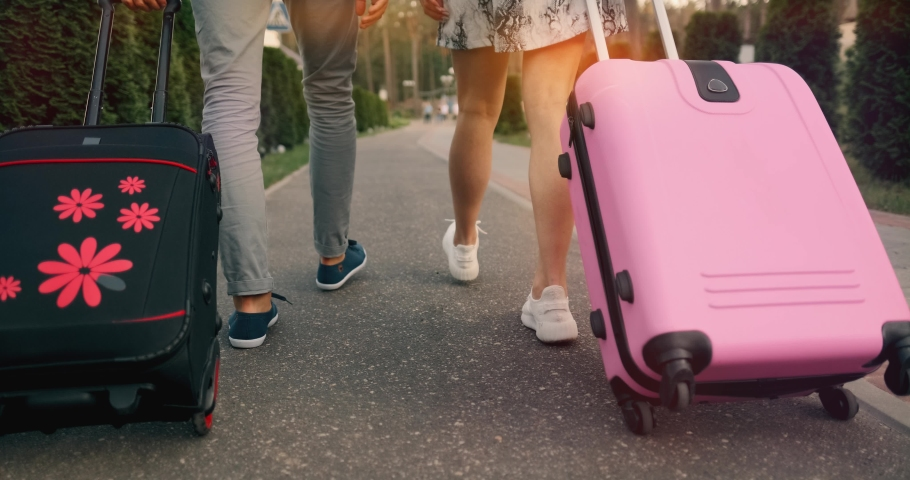 Young couple lovers walking down the street with their suitcases. Friends tourists with luggage are ready for travel and go to the plane or hotel. | Shutterstock HD Video #1032565226