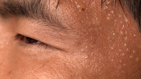 This close up macro video shows a nervous asian man's sweating skin.