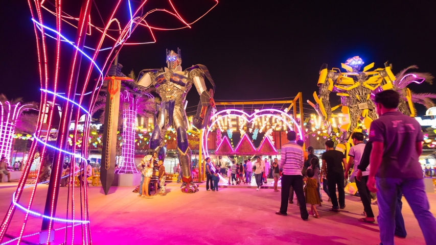 SIEM REAP, CAMBODIA - APRIL 9, 2019: Timelapse of two high robots in brightly decorated theme park at night market