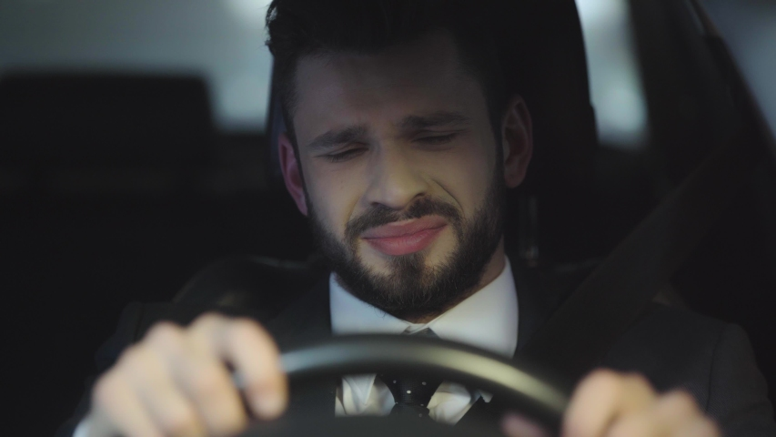 Selective focus of upset bearded man crying while driving car | Shutterstock HD Video #1032683216
