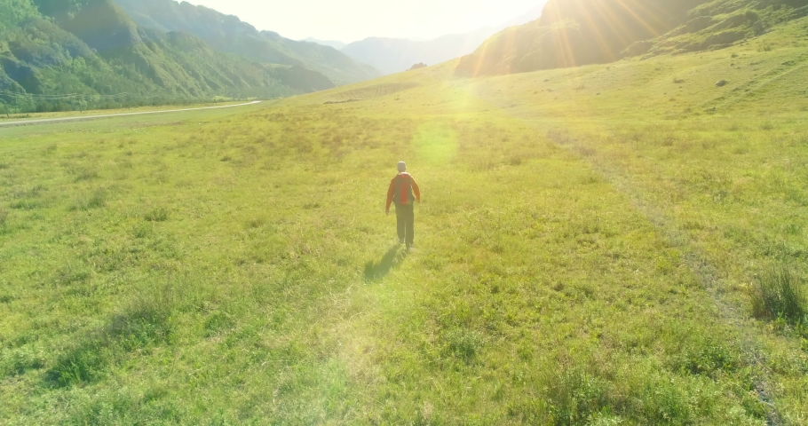 Aerial 4K UHD view. Low altitude flight over young man tourist walking across green mountain field. Huge rural valley and sunny meadow at summer day. Backpack hiking guy. | Shutterstock HD Video #1032787136