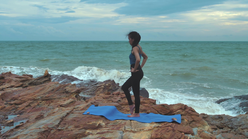 Asian women practicing yoga relax in nature at seaside in the evening. Fitness and healthy lifestyle concept. Slow Motion #1032811916