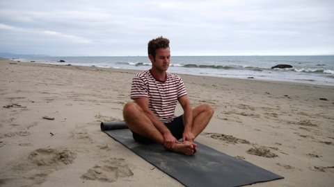 A man stretching on a mat before practicing a yoga pose on the beach with ocean waves in California SLOW MOTION.