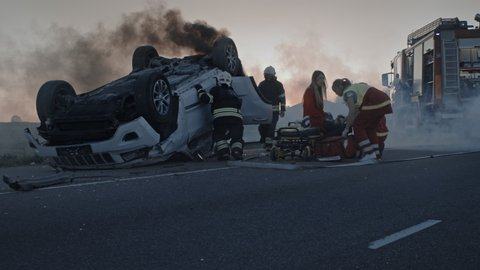 Car Crash Traffic Accident: Paramedics and Firefighters Rescue Injured Trapped Victims. Medics give First Aid to a Shocked Female Passenger Stretchers. Firemen Use Hydraulic Cutters Spreader