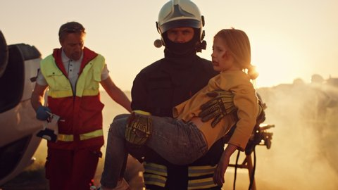 Brave Firefighter Carries Injured Young Girl to Safety. In the Background Car Crash Traffice Accident with Courageous Paramedics and Firemen Save Lifes, Fight Fire